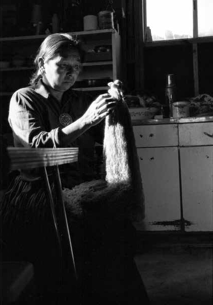 Mae Tso, Diné cleans wool from her sheep for rug weaving at her home in Big Mountain on the Navajo Reservation in Arizona, 1986(Navajo)
